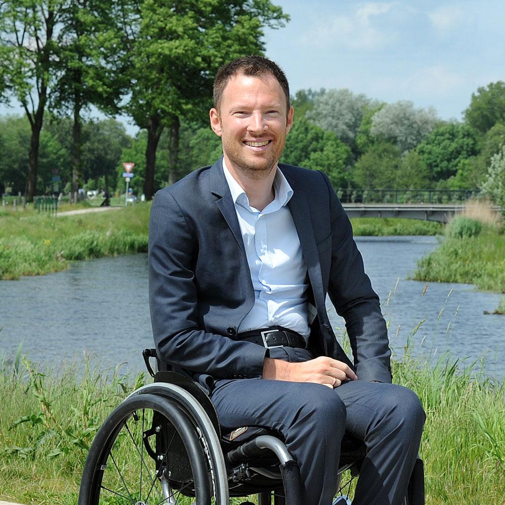 Een foto van dagvoorzitter Otwin van Dijk, glimlachend in de buitenlucht.